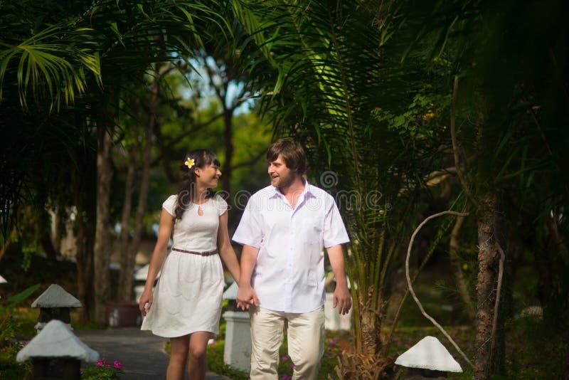 Lycklig brud och brudgum som går i rainforesten royaltyfri foto