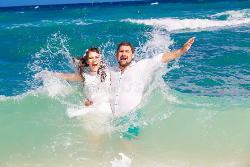 Lycklig brud och brudgum som har gyckel i vågorna på en tropisk beac royaltyfri fotografi