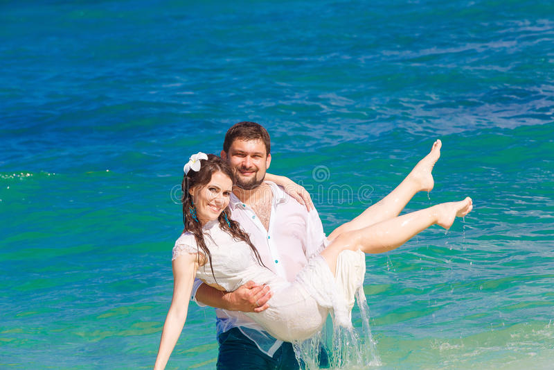 Lycklig brud och brudgum som har gyckel i vågorna på en tropisk beac arkivfoto