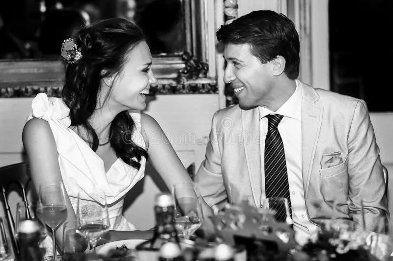 Lycklig brud och brudgum som ler blick och i en restauran royaltyfri bild