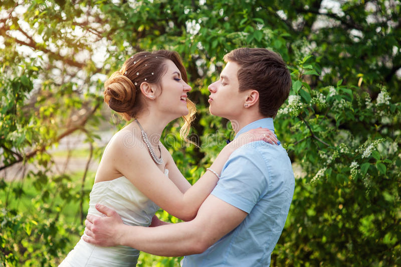 Lycklig brud och brudgum som på våren kysser trädgården royaltyfria bilder