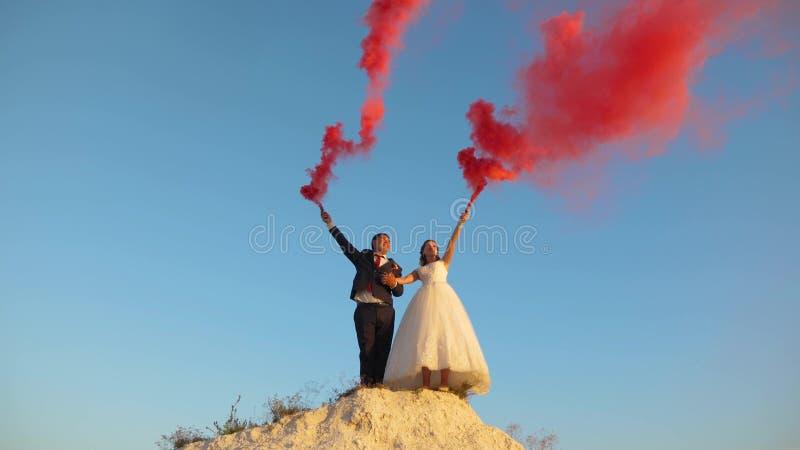 Lycklig brud och brudgum som vinkar kulör rosa rök mot blå himmel och att skratta bröllopsresa roman förhållande between arkivfoto