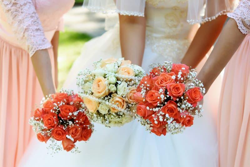 Lycklig brud och brudtärnor som visar deras lyxiga buketter på gor royaltyfri fotografi