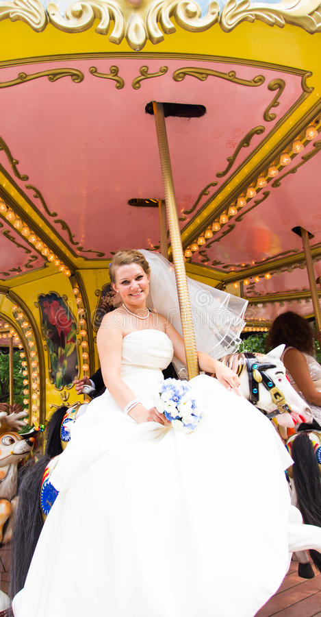 Lycklig brud på en karusell royaltyfria bilder