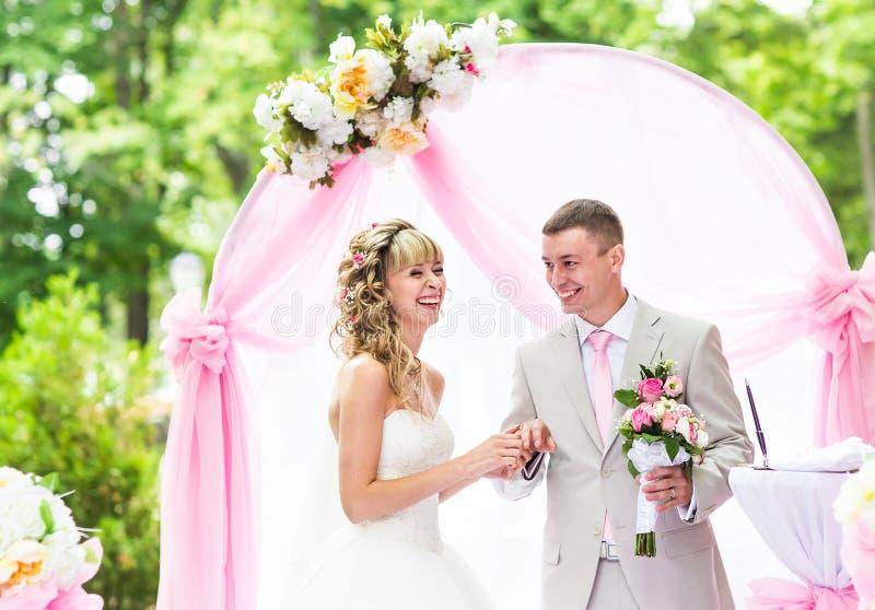 Lycklig brud som sätter en cirkel på brudgums finger under bröllopceremoni royaltyfri fotografi