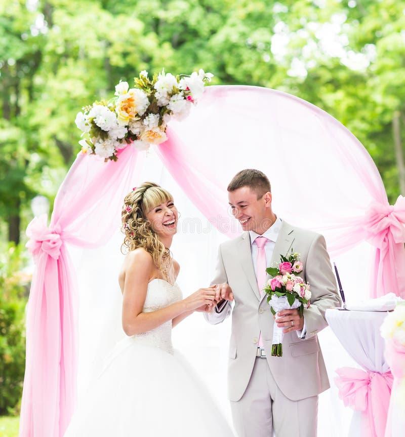 Lycklig brud som sätter en cirkel på brudgums finger under bröllopceremoni royaltyfri bild