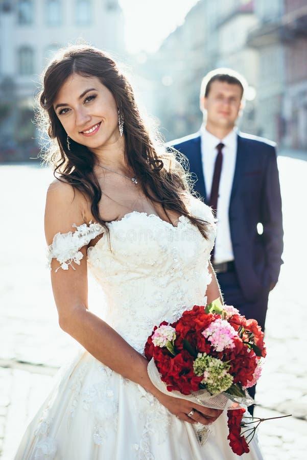 lycklig brudbrunett Hon rymmer bröllopbuketten av röda och rosa färgblommor på bakgrunden av den stående brudgummen royaltyfria foton