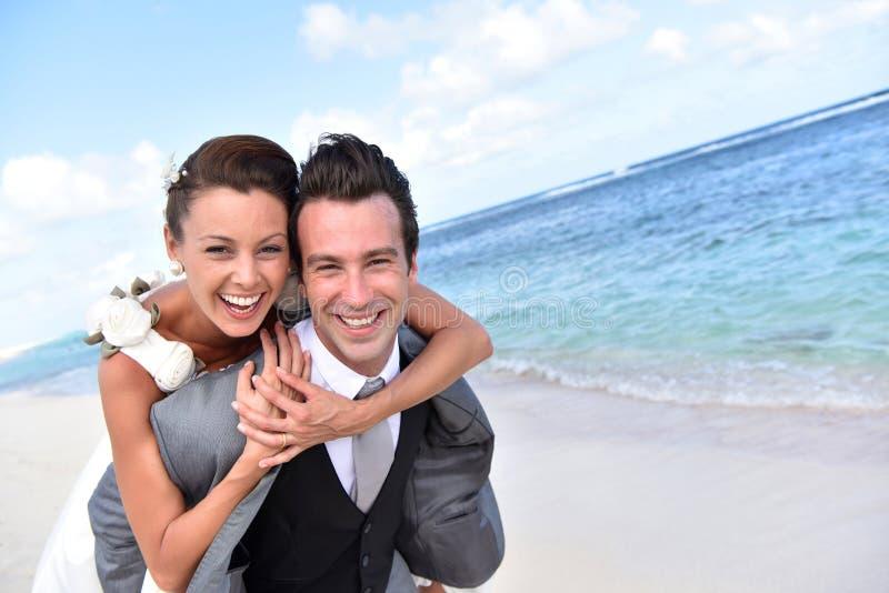 Lycklig brudgum och brud på stranden som har gyckel arkivfoton