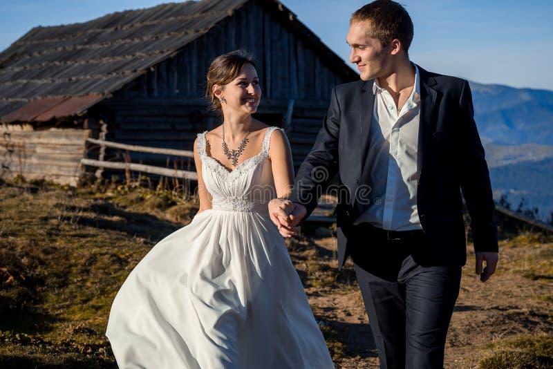 Lycklig brudgum och brud som går på bergbygden solig dag royaltyfri foto