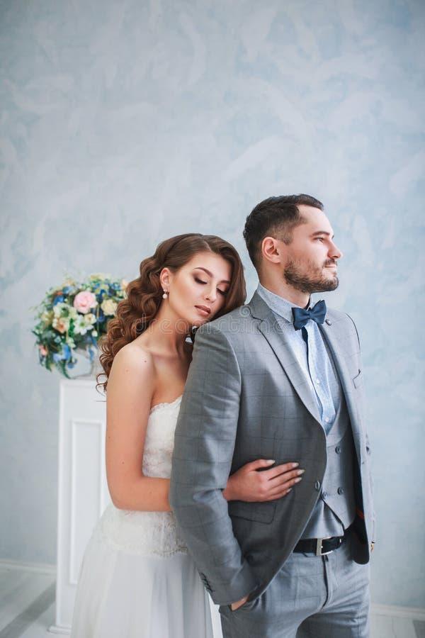 Lycklig brudgum och brud som poserar på en studio med den härliga blommadekoren krama för par royaltyfri fotografi