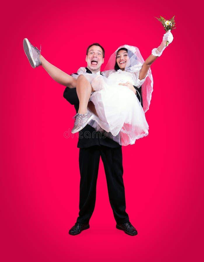 Lycklig brudgum som rymmer bruden i hans armar fotografering för bildbyråer