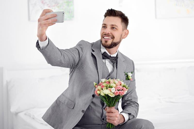 Lycklig brudgum som tar selfie fotografering för bildbyråer