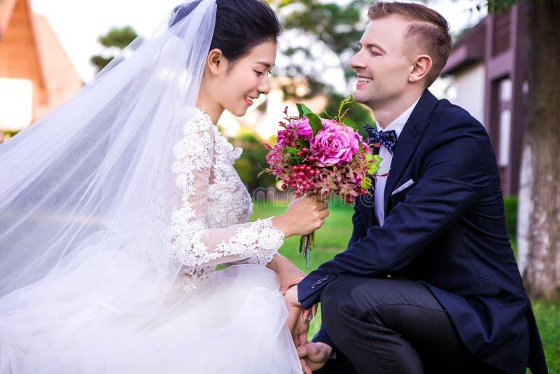 Lycklig brudgum som utomhus ser den hållande buketten för härlig brud royaltyfria bilder