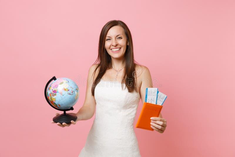 Lycklig brudkvinna i det vita jordklotet för bröllopsklänninginnehavvärld, biljett för passlogipasserande som utomlands går för b royaltyfri fotografi