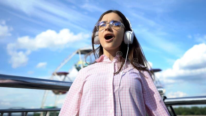 Lycklig brunettkvinna i hörlurar som lyssnar till musik och sjunger på pir, gyckel arkivbilder