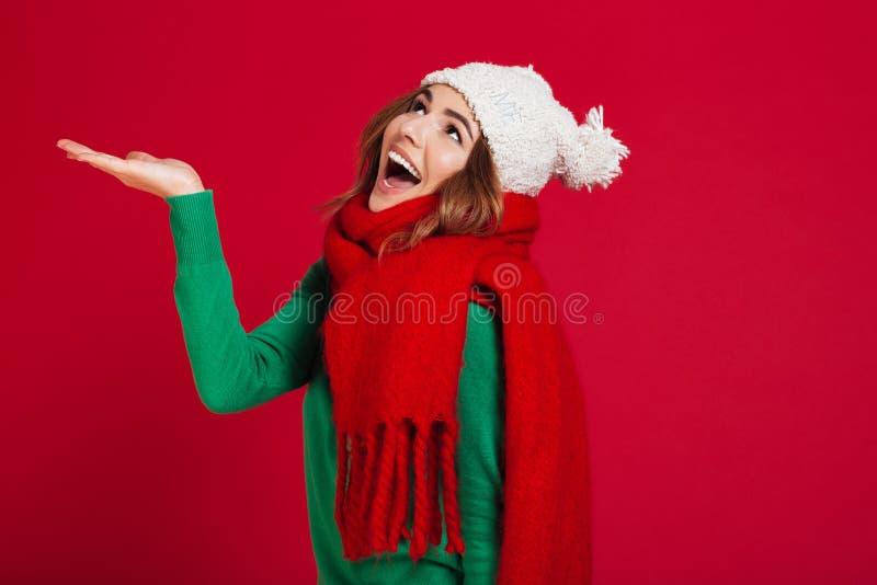 Lycklig brunettkvinna i tröja, rolig hatt och halsduk royaltyfria bilder