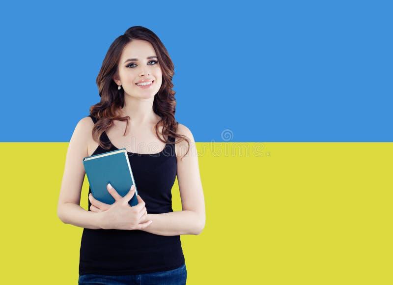Lycklig brunettkvinna på den ukrainska flaggabakgrunden Lämna i Ukraina och talande ukrainskt språk arkivbilder
