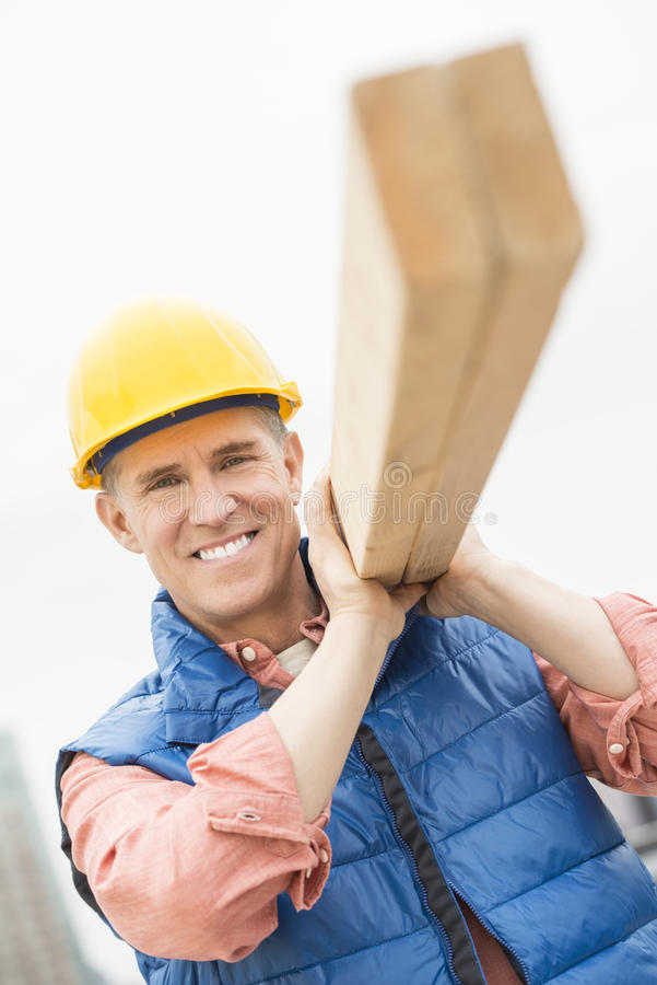 Lycklig byggnadsarbetare Carrying Wooden Plank royaltyfri foto