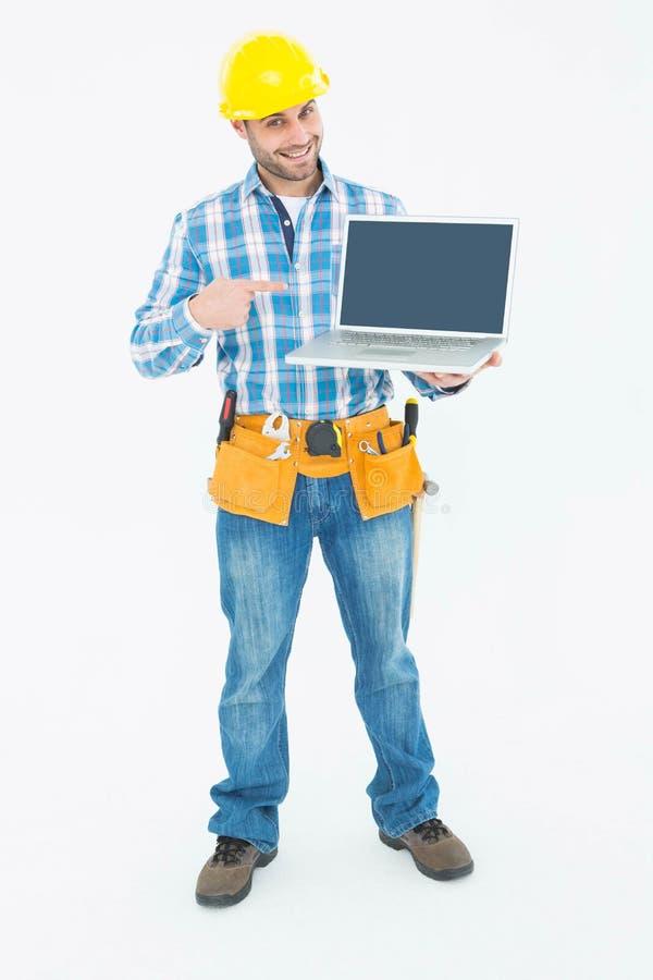 Lycklig byggnadsarbetare som pekar på bärbara datorn arkivbild