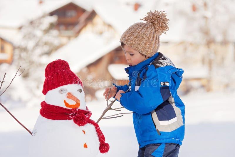Lycklig byggnadssnögubbe för härligt barn i trädgården, vinter arkivfoto