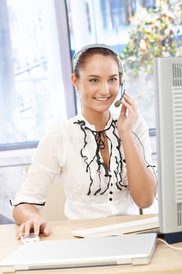 Lycklig callcenteroperatörsflicka på skrivbordet royaltyfri fotografi