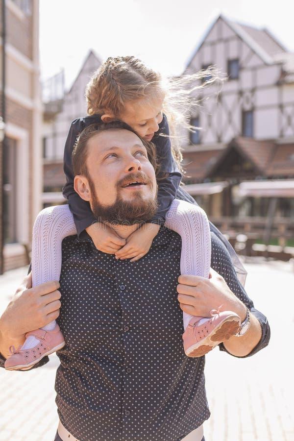 Lycklig caucasian familj av fadern och dottern på en gå i den europeiska staden, iklädd tillfällig dräkt Sommardagsljus royaltyfri fotografi