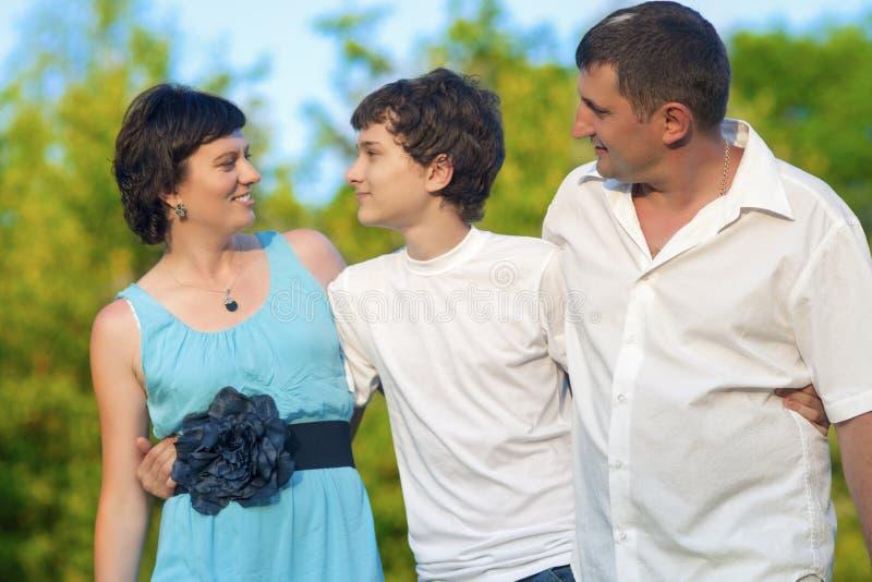 Lycklig Caucasian familj av tre spendera Tid tillsammans Att gå som in omfamnas, parkerar royaltyfri fotografi