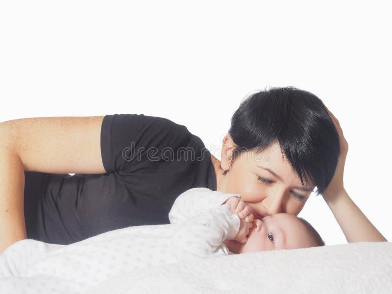 Lycklig caucasian familj som ligger på den isolerade sängen royaltyfria foton