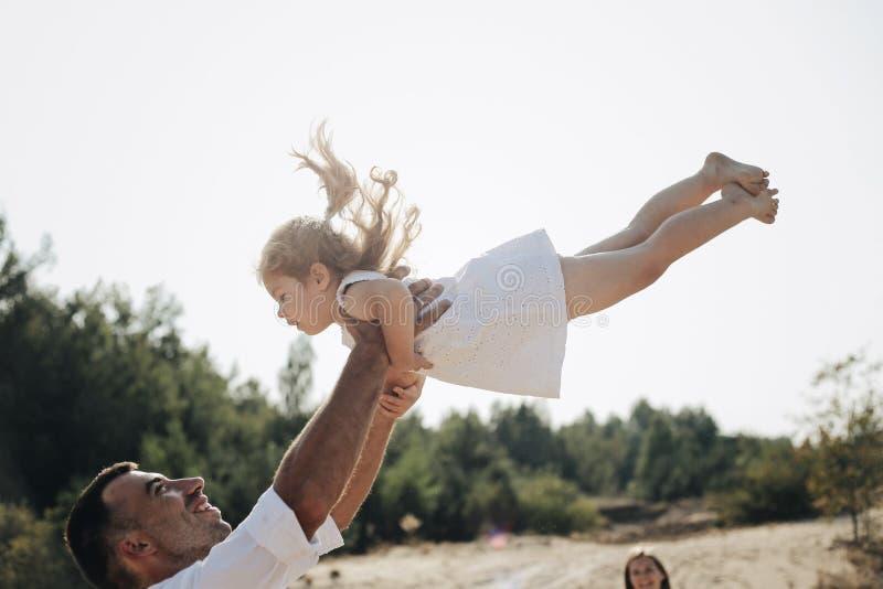 Lycklig caucasian farsa och hans liten dotter som har roligt Fadern kastar den söta dottern i den vita klänningen i luften arkivfoto