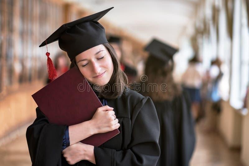 Lycklig caucasian kvinna på hennes avläggande av examendag på universitetet arkivbilder