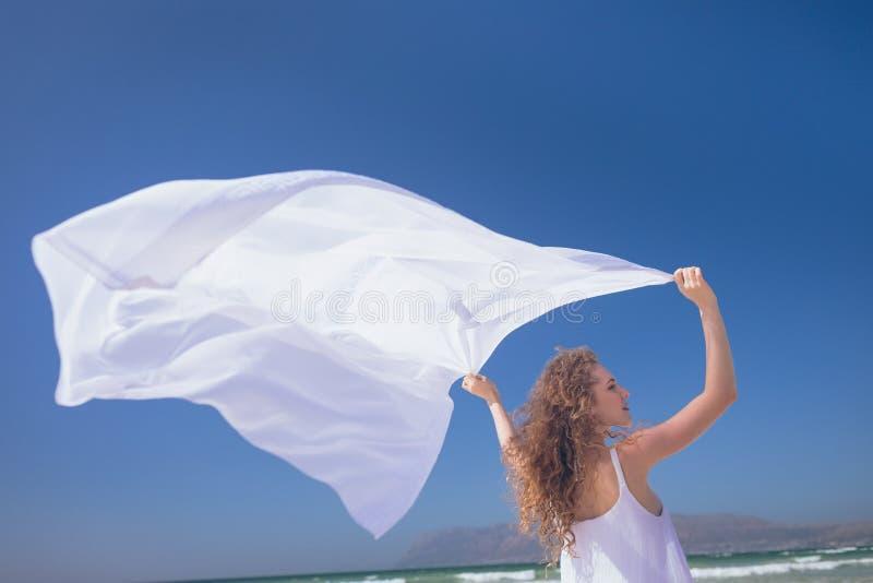 Lycklig Caucasian kvinnainnehavhalsduk på stranden royaltyfri foto