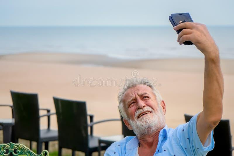 Lycklig caucasian man som använder smartphonen för pratstund och selfie fotografering för bildbyråer