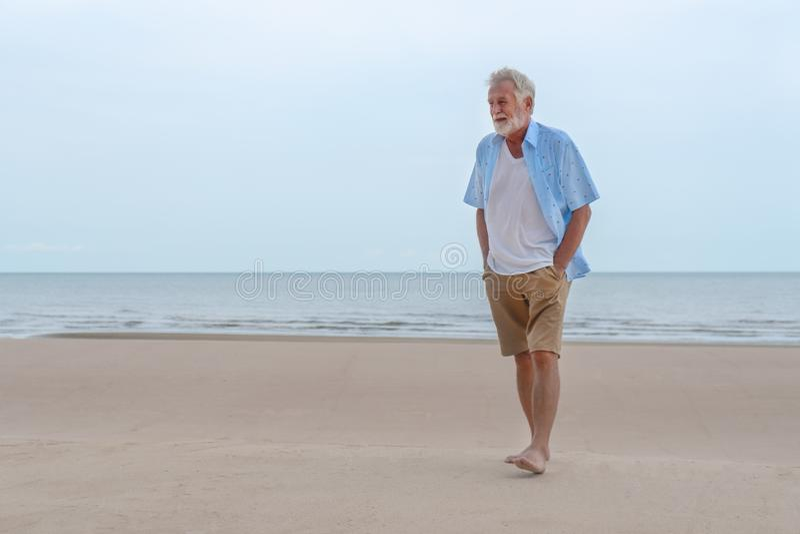 Lycklig caucasian manlig avslappnande och promenera strand royaltyfri bild