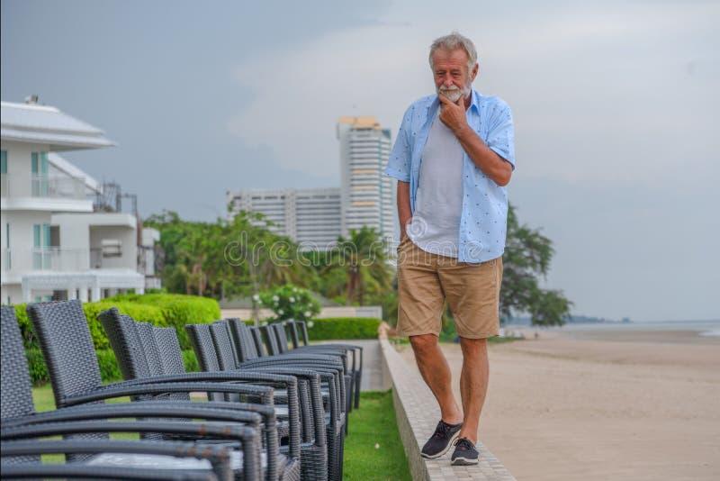 Lycklig caucasian manlig avslappnande och promenera strand arkivfoto