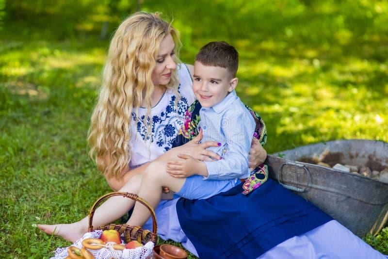 Lycklig Caucasian moder med hennes lilla unge Posera med korgen som är full av brödcirklar utomhus royaltyfri foto