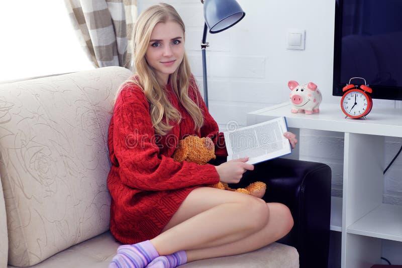 Lycklig Caucasian tonårig flicka som vilar på soffan på vardagsrummet medan läsebok fotografering för bildbyråer