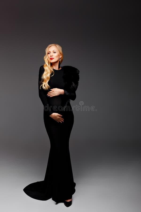 Lycklig chic ung gravid kvinna i stilfull svart bula för klänninginnehavbuk och posera i ljus Stilfull trendig mamma som kramar arkivfoton