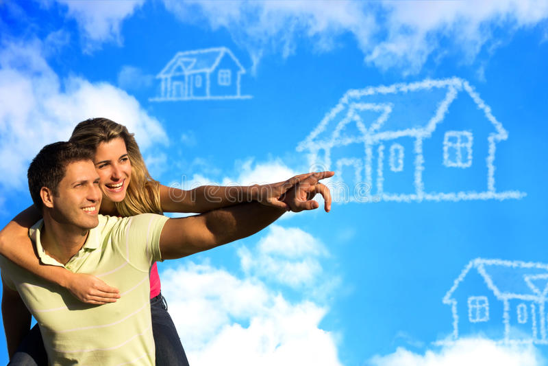 Lycklig coupleunder den blåa himlen som drömmer av ett hus. royaltyfri fotografi