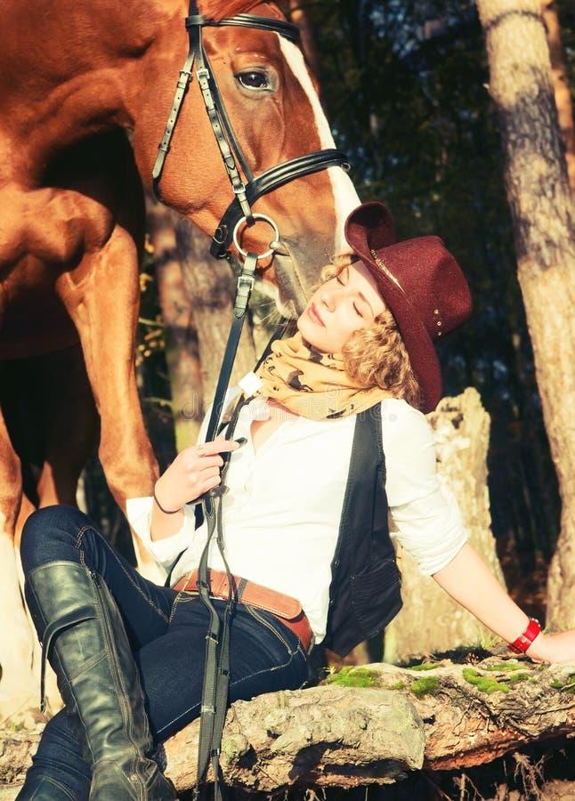 Lycklig cowgirl med henne röd häst. royaltyfria bilder