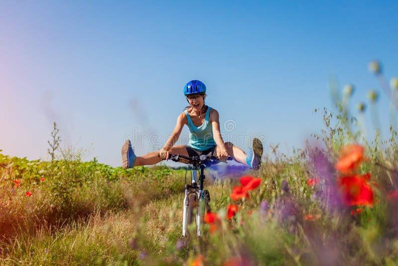 Lycklig cyklist för ung kvinna som rider en bergcykel i sommarfält Flicka som har gyckellyftande ben royaltyfri foto