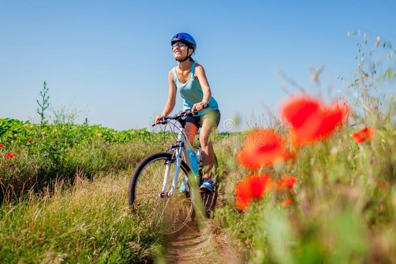Lycklig cyklist för ung kvinna som rider en bergcykel i sommarfält Flicka som har gyckellyftande ben arkivbilder