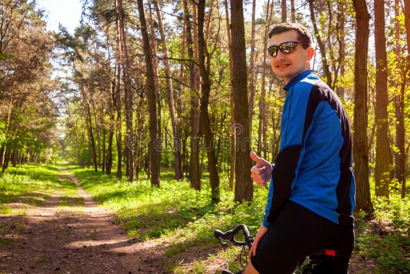 Lycklig cyklist för ung man som rider en vägcykel i hand för visning för vårskogman med tummen upp royaltyfri foto