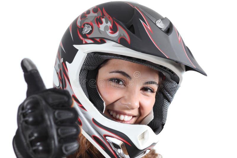 Lycklig cyklistkvinna med en motocrosshjälm och tumme upp royaltyfri bild