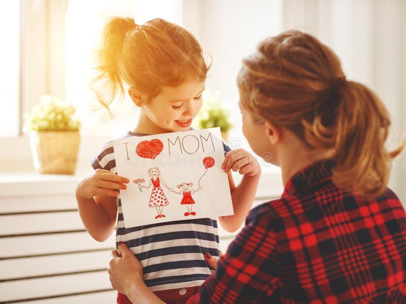 Lycklig dag för moder` s! Dottern ger hennes moder en vykort fotografering för bildbyråer