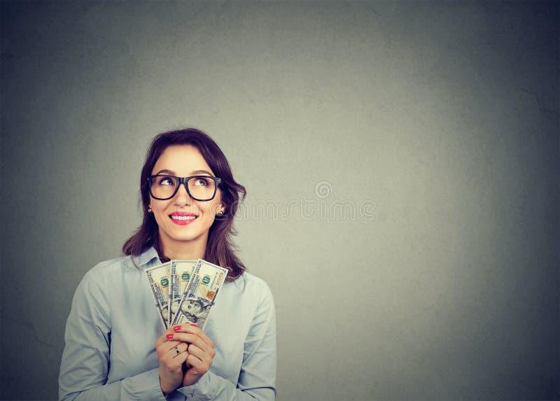 Lycklig dagdrömma affärskvinna med pengardollarräkningar i hand som föreställer hur man spenderar dem royaltyfri bild
