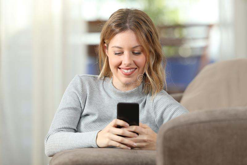 Lycklig dam som hemma smsar på telefonen på en soffa royaltyfria bilder