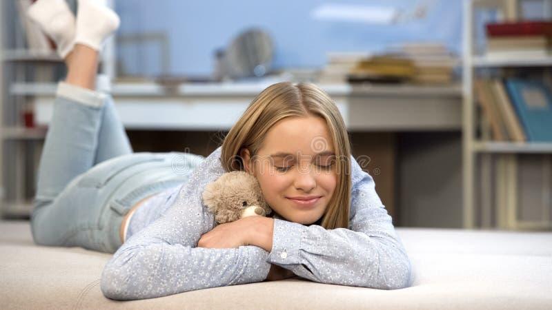 Lycklig dam som kramar hennes nalle i sovrummet, favorit- leksak som minns barndom arkivbild