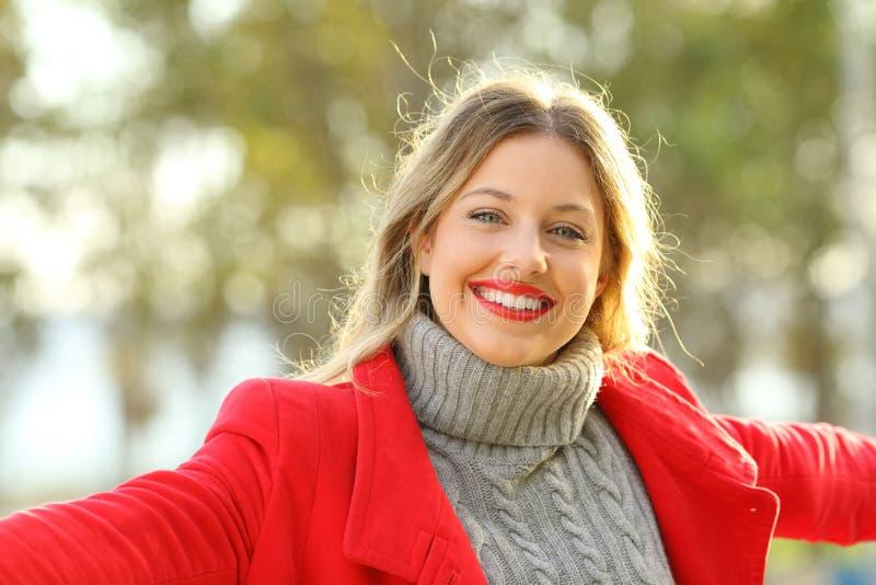 Lycklig dam som poserar se kameran i vinter royaltyfri foto