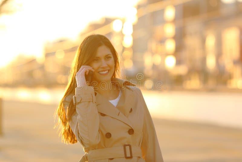 Lycklig dam som talar på telefonen på solnedgången i en stad arkivbild