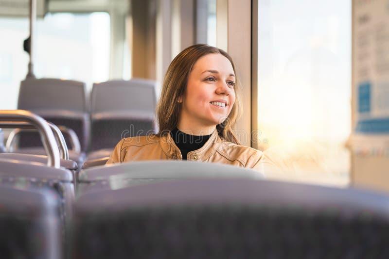 Lycklig dam som ut ser fönstret i buss, drev, spårvagn eller gångtunnel arkivfoto